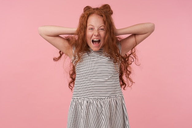 Overjoyed lovely curly female kid with long foxy hair holding her head with raised palms, screaming happily and looking at camera with raised eyebrows, posing over pink background