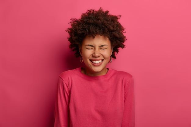 기뻐하는 사랑스러운 여성은 행복에서 웃고, 칭찬과 따뜻한 말을 듣고 기뻐하며, 넓게 웃으며 밝은 진홍색 점퍼를 입습니다.