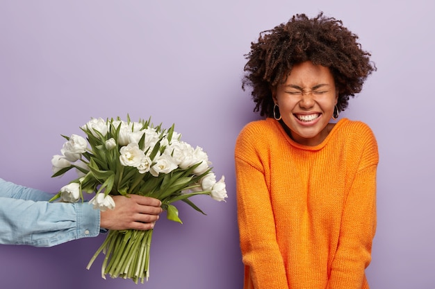 Felicissima e adorabile giovane signora afroamericana riccia riceve congratulazioni e fiori per il compleanno, un uomo irriconoscibile allunga le mani e dà tulipani bianchi primaverili, isolati su un muro viola.