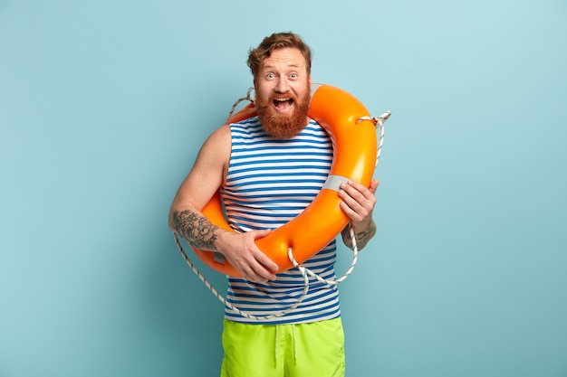 Overjoyed male lifeguard with tattoo, foxy beard, poses with inflated rescue ring, prevents accident on water, wears summer clothes