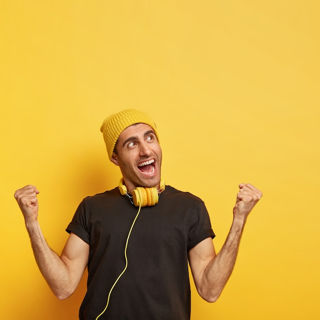 Overjoyed man raises clenched fists, feels energized and upbeat, wears yellow hat and black t shirt, gestures happily, listens music in headphones