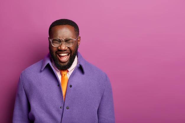 暗いきれいな肌を持つ大喜びの男は大声で笑い、喜びで目を閉じ、自由時間中に面白い話を聞き、眼鏡と紫色のジャケットを着ています