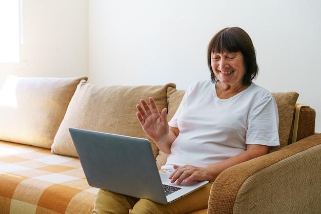 現代のラップトップでビデオ通話で話しているリビングルームのソファに座って大喜びの成熟した女性幸せなe ...
