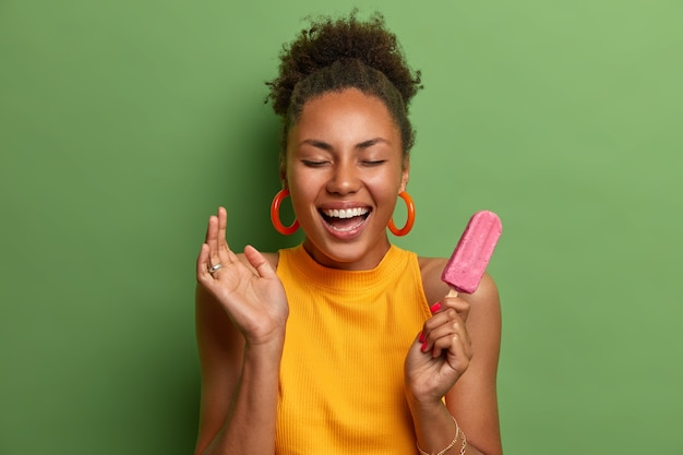 Overjoyed millennial woman with combed curly hair smiles broadly has fun and eats delicious strawberry ice cream