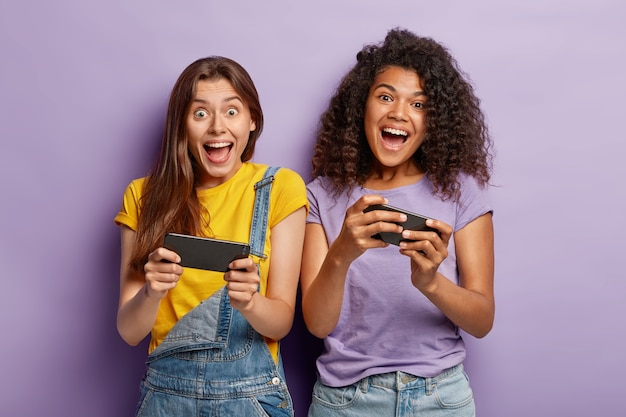 Felicissime blogger di razza mista ridono e comunicano con i follower sui telefoni cellulari