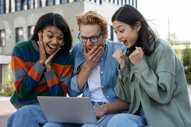 オンラインショッピングのラップトップコンピュータを使用して大喜びの多民族の友人