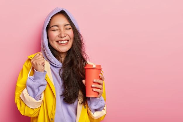 大喜びの喜んでいるアジアの女性は、くいしばられた握りこぶしを上げ、目を閉じて、フラスコから温かい飲み物を飲み、幸せな瞬間を喜んで、暖かい防水服を着ています