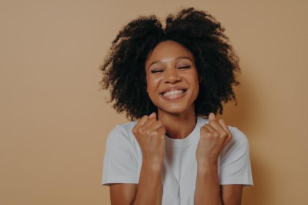 Обрадованная, довольная темнокожая молодая женщина поднимает сжатые кулаки, показывает белые зубы, носит повседневную белую футболку, модели изолированы на пастельно-бежевом фоне с копией пространства, празднует отличные новости