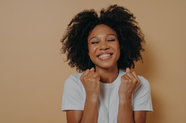 Overjoyed pleased dark skinned young woman raises clenched fists, shows white teeth, wears casual white tshirt, models isolated over pastel beige background with copy space, celebrates excellent news