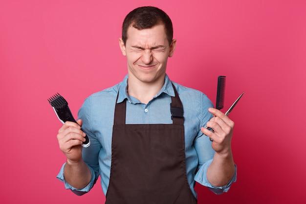 Обрадованный довольный мужчина щурит лицо, держит электробритву, ножницы, расческу для волос, готов сделать прическу, держит глаза закрытыми