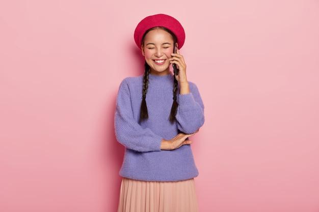 아시아 외모를 가진 기뻐서 기뻐하는 여성, 친구와 재미있는 전화 대화를 즐기고, 귀 근처에 현대 세포를 유지하고, 두 개의 긴 땋은 머리가 있습니다.
