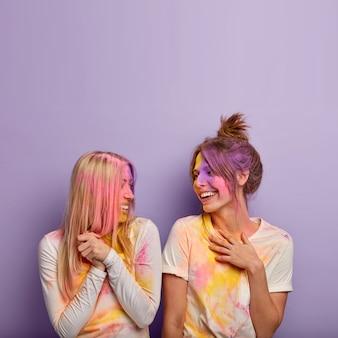 Обрадованные, довольные женщины устраивают цветную вечеринку холи, вместе разыгрывают, смеются позитивно, наслаждаются празднованием весенних праздников, смотрят друг на друга, изолированные над фиолетовой стеной с пустым пространством наверху.