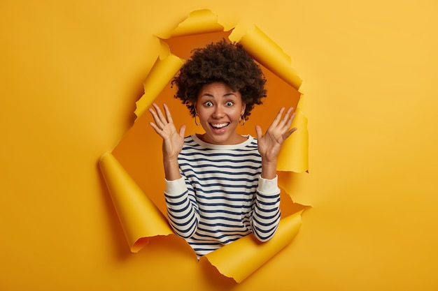 Overjoyed pleased young african american lady keeps both hands raised, glad to hear something awesome, grins at camera happily, wears striped jumper, poses through yellow torn hole.
