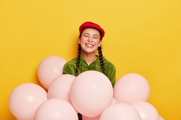 Overjoyed pretty chinese woman wears red beret, corduroy sweatshirt, poses with air balloons