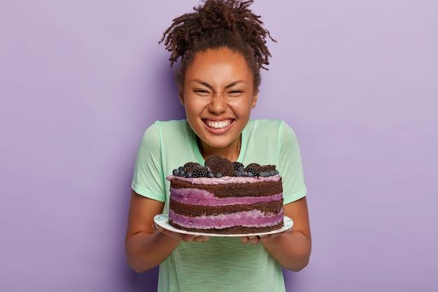 大喜びのきれいな女性は、大きなおいしい食欲をそそるケーキでプレートを保持します