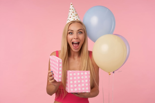 Overjoyed pretty young blonde woman lady with casual hairstyle showing happy reaction on getting awesome present, posing over pink background in birthday hat,looking at camera with wide cheerful smile