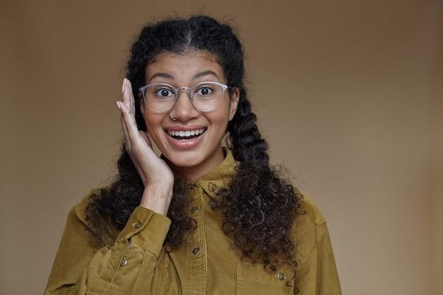 제기 눈썹으로 행복하게보고 유쾌하게 웃고, 고립 된 꼰 헤어 스타일로 기뻐 꽤 젊은 갈색 머리 어두운 피부 여성