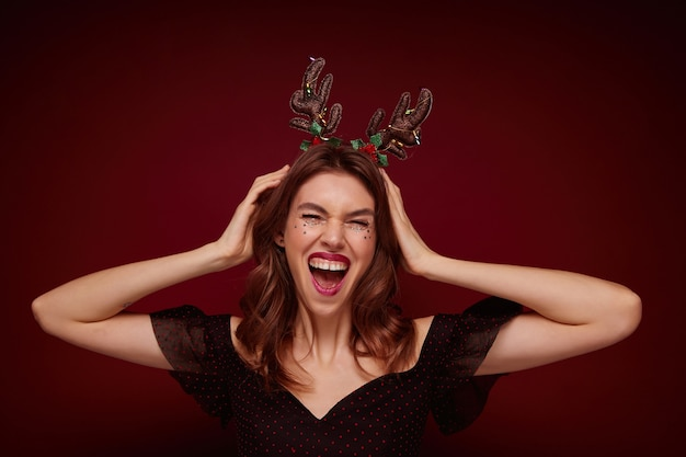 기뻐하는 우아한 옷을 입고 물결 모양의 헤어 스타일을 가진 꽤 젊은 갈색 머리 여자가 기뻐하고, 재미있는 휴가 후프를 착용하고 행복하게 웃고 있습니다.