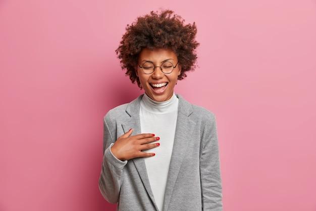 Felicissima manager donna professionista non riesce a smettere di ridere, sente battute divertenti da un collega, indossa abiti da lavoro, ridacchia positivamente