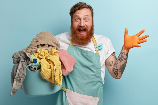 Overjoyed red haired man with foxy thick beard, raises hand, being very happy, wears casual t shirt and apron, holds basin full of laundry, has tattooed arm busy with domestic chores, glad finish work