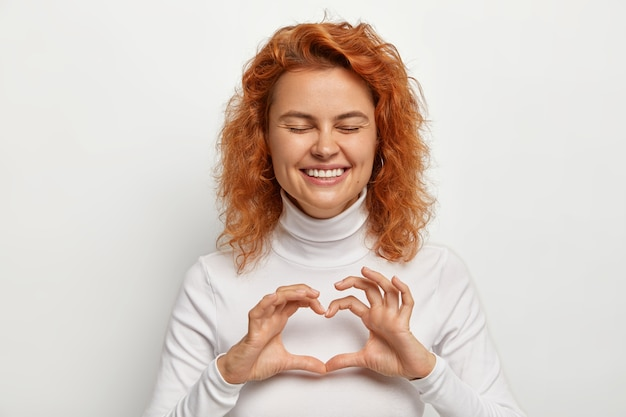 Overjoyed redhead curly woman laughs positively, shares love with you, makes heart sign with hands over chest, expresses affection, keeps eyes shut from pleasure, dressed in white casual outfit