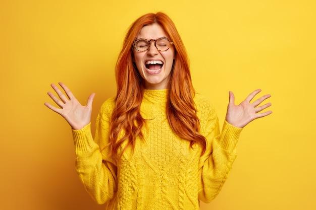 기뻐하는 빨간 머리 여자는 큰 소리로 웃음을 지으며 손바닥을 뻗어 웃음을 터 뜨리고 눈을 감고 입을 크게 벌리고 캐주얼 점퍼를 착용합니다.