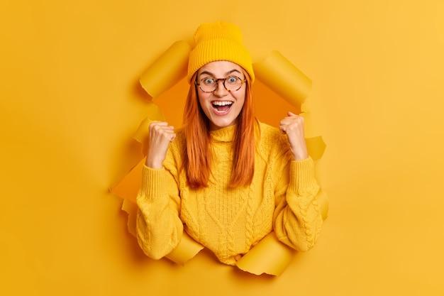 Giovane donna rossa felicissima stringe i pugni celebra il successo esclama felicemente indossa cappello giallo e suda