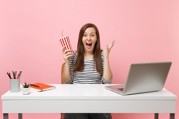 분홍색 배경에 격리된 pc 노트북이 있는 흰색 책상에서 콜라나 탄산음료가 든 플락틱 컵을 들고 손을 벌리고 있는 충격을 받은 여성이 크게 기뻐했습니다. 성취 비즈니스 경력 개념입니다. 공간을 복사합니다.
