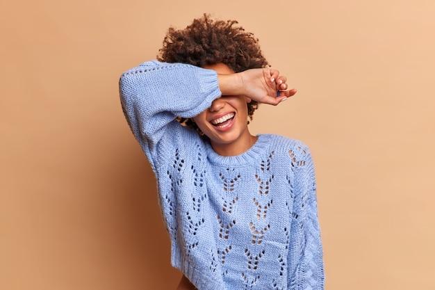 기뻐하는 수줍은 여자가 팔 미소로 눈을 숨기고 베이지 색 벽 위에 고립 된 파란색 스웨터를 입은 놀라움을 기다립니다.