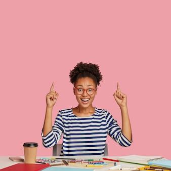 Ragazza studentessa felicissima in posa alla scrivania contro il muro rosa
