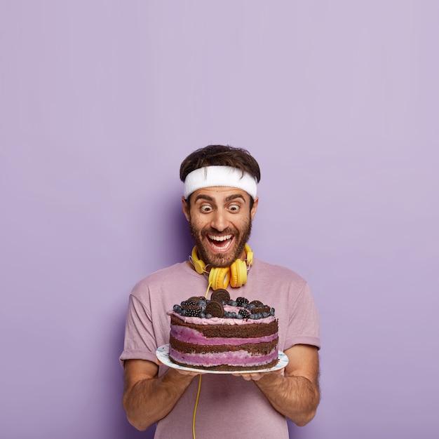 大喜びの驚いた男はおいしいケーキを見つめ、誘惑を感じ、活発な運動の後に空腹になり、カジュアルなtシャツを着て、ヘッドフォンを持っています