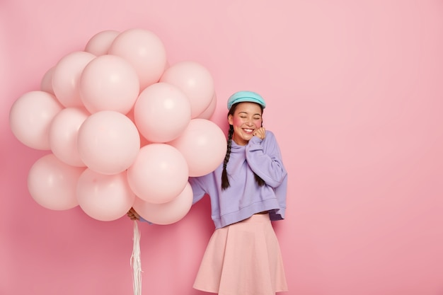 Overjoyed teenage girl keeps eyes closed, smiles broadly, shows white teeth, wears beret, sweatshirt and skirt, holds inflated balloons, celebrates getting bachelors degree, isolated on rosy wall