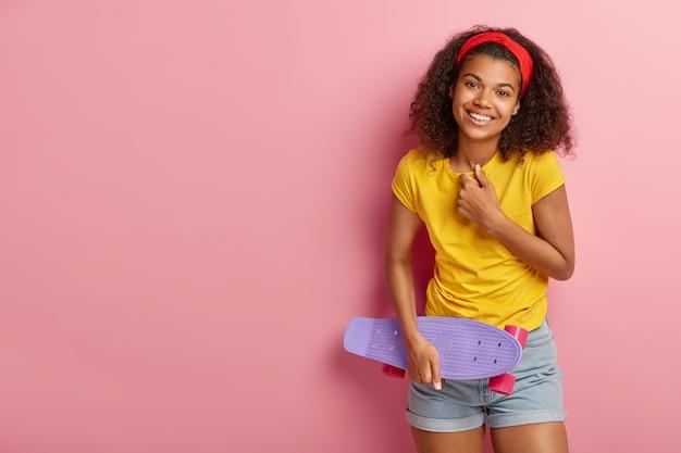 大喜びの10代の少女は前向きに笑い、気分が良く、気持ちの良い感情を表現し、カジュアルな夏の服を着て、ロングボードを持ち、友達と楽しんでいます
