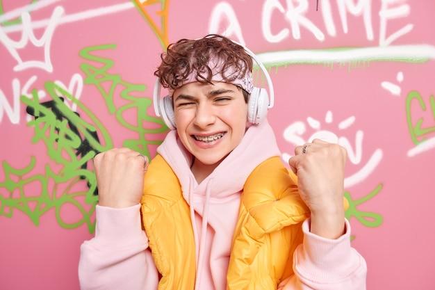 Обрадованный подросток с кудрявыми волосами, сжимающий кулаки, празднует успех, одетый в модную одежду, любит слушать музыку через беспроводные наушники, позирует на стене с граффити Premium Фотографии