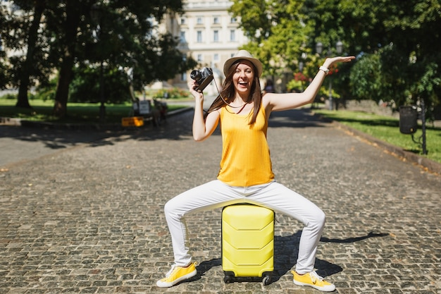 Overjoyed traveler tourist woman in casual clothes sit on suitcase with retro vintage photo camera spread hands in city outdoor. girl traveling abroad on weekends getaway. tourism journey lifestyle.