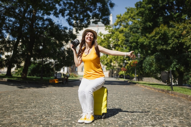Overjoyed traveler tourist woman in hat sitting on suitcase holding retro vintage photo camera spreading hands in city outdoor. girl traveling abroad on weekend getaway. tourism journey lifestyle.