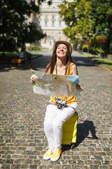 노란색 옷 모자를 쓴 여행자 관광 여성이 도시 야외에서 도시 지도 검색 경로를 들고 여행 가방에 앉아 기뻐했습니다. 주말 휴가를 여행하기 위해 해외로 여행하는 소녀. 관광 여행 라이프 스타일.