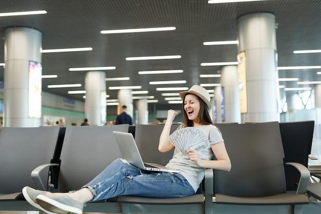 ラップトップで働いている大喜びの旅行者の観光客の女性は、空港のロビーホールで勝者のジェスチャーを待つドルの束を保持します