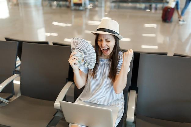 ノートパソコンで作業している大喜びの旅行者の観光客の女性は、空港のロビーホールで勝者のジェスチャーを待つドルの束を保持しています