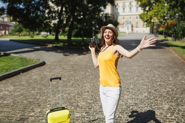 Overjoyed traveler tourist woman in yellow casual clothes with suitcase holding retro vintage photo camera spreading hands outdoor. girl traveling abroad on weekend getaway. tourism journey lifestyle.