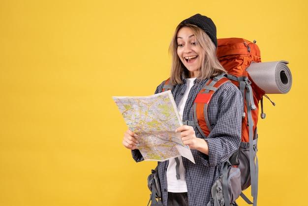 Donna viaggiatrice felicissima con lo zaino che guarda la mappa