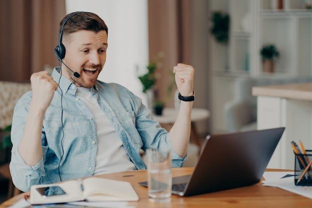大喜びの勝利の大人の男が拳を食いしばって成功を祝うノートパソコンの画面を注意深く見つめるヘッドセットは、ぼやけた家の背景に対してデスクトップで企業の会議のオンラインポーズを持っています