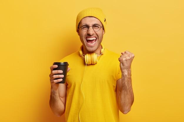 Обрадованный победоносный хипстер сжимает кулак, удовлетворенно восклицает, держит кофе на вынос, носит наушники на шее