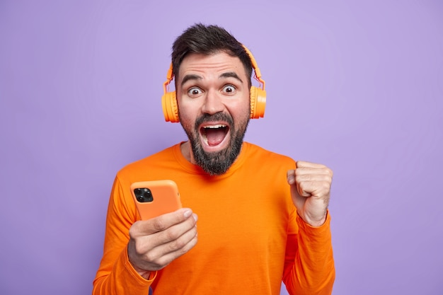 Overjoyed unshaven man celebrates excellent news clenches fist holds mobile phone uses wireless headphones for listening music enjoys good sound wears orange jumper