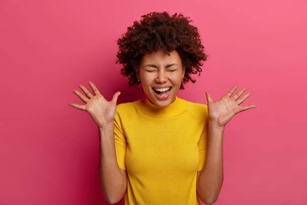 Overjoyed upbeat millennial girl laughs and raises palms, has very happy face expression, watches funny scene, dressed in yellow t-shirt, isolated on pink wall. positive emotions concept