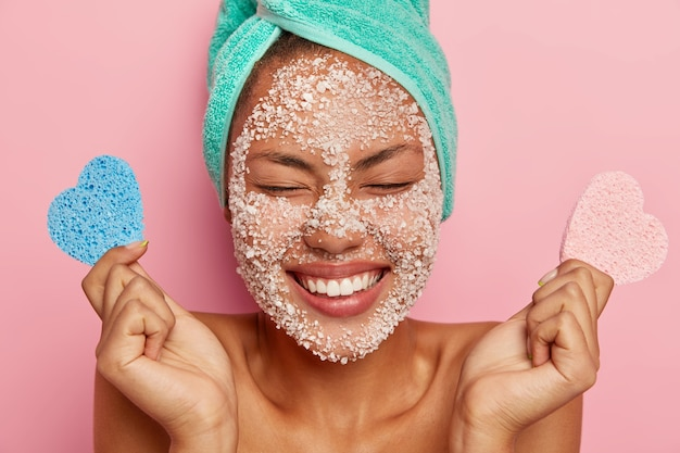 Overjoyed woman closes eyes with pleasure, smiles broadly, gets facial treatment in beauty center holds two makeup sponges poses on pink studio wall