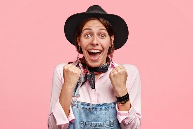 기쁜 표정으로 기뻐하는 여성 농부, 주먹을 쥐고, 정원 구매를 축하하고, 캐주얼 한 옷을 입습니다.