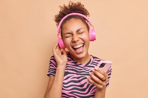 大喜びの女性は楽しいです耳にピンクのワイヤレスヘッドフォンを着用して音楽を聴くのを楽しんでいますベージュの壁の上に幸せに隔離された現代のスマートフォンの笑いを保持します