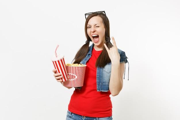 ポップコーンのバケツ、角のジェスチャーを示すソーダコーラのプラスチックカップ、白い背景で隔離の重金属のロックサインを描いた映画を見ている3dメガネで大喜びの女性。映画の感情。