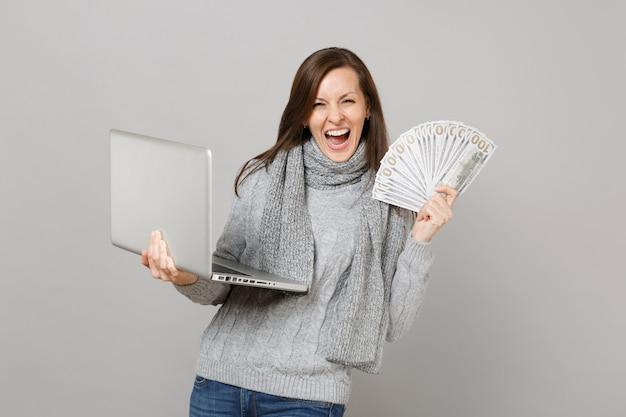 ラップトップpcコンピューターで作業しているセーターの大喜びの女性は灰色の背景に分離されたたくさんのドル紙幣現金お金を保持します。寒い季節のコンセプトをコンサルティングする健康的なライフスタイルのオンライン治療。